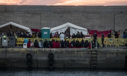 People sit in Arguineguín shortly after being rescued when a boat capsized near Lanzarote earlier this month. At least seven died.