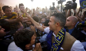 Robin van Persie is mobbed by Fenerbahce fans after arriving at Istanbul's Sabiha Gokcan Airport in July.