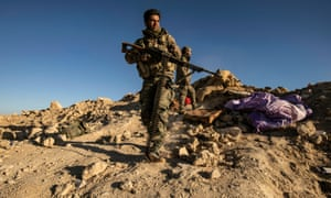 Fighters with the Syrian Democratic Forces (SDF) keep position at a hilltop overlooking Isis in the village of Baghuz on 18 March 2019.