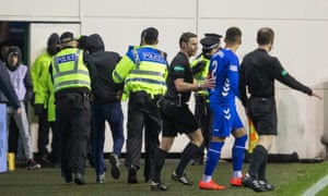 Police lead the fan away from the pitch