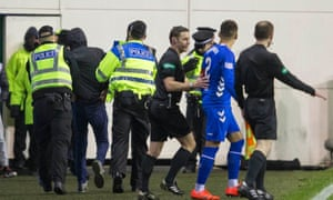 Police lead a fan away from the pitch after the Rangers captain James Tavernier was accosted at Easter Road.