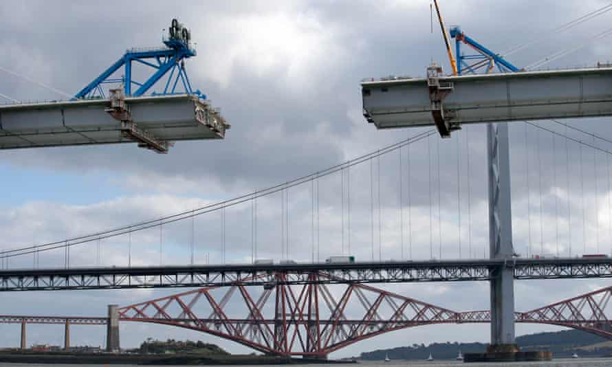 Work is carried out on the central sections of  Queensferry Crossing, with the old Forth road and Forth railway bridges in the background.