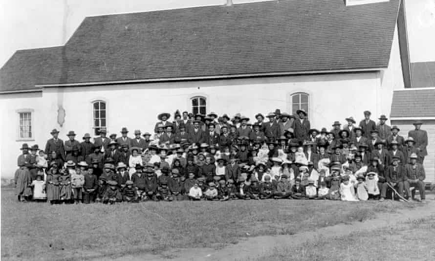 A photo dated c 1910 of the Marieval mission church and its congregation as it stood next to the Marieval Indian residential school, Canada.