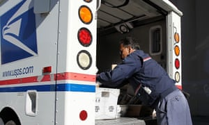 A US postal service letter carrier arranges mail in his truck.