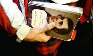 a tartan-clad man holds a collection of Robert Burns's poetry.