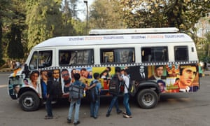 Schoolchildren touch photographs of Indian filmstars adorning a tour van inside Film City in Mumbai, India