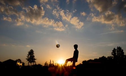 Silhouette of a teenage boy playing football
