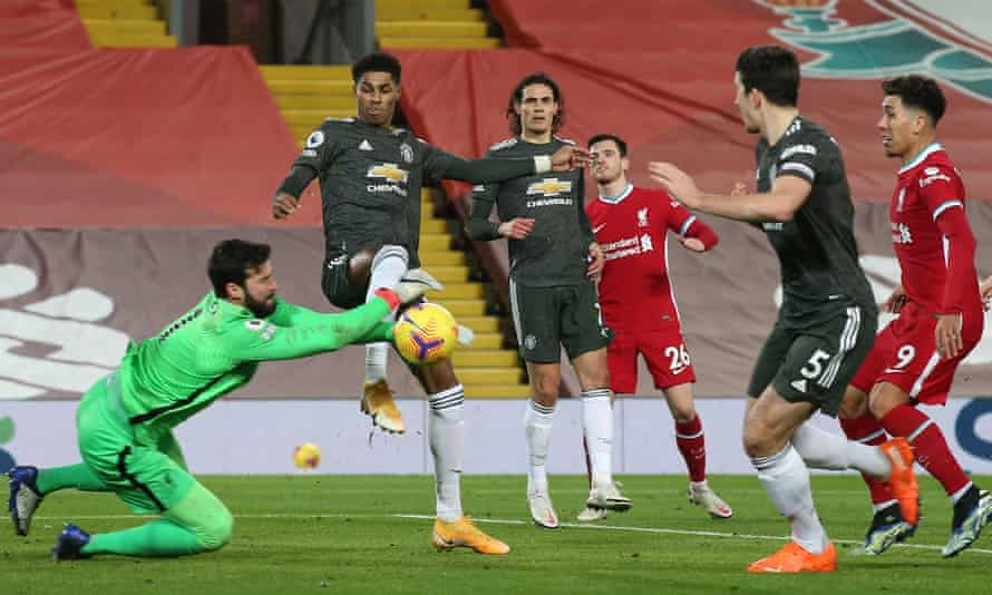 The Liverpool goalkeeper, Alisson, gets to the ball ahead of Manchester United's Marcus Rashford.
