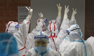 Medical staff cheer themselves up before going into an ICU ward for coronavirus patients at the Red Cross Hospital in Wuhan, China on March 16, 2020.