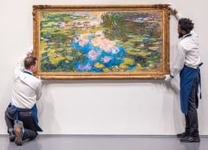 Sotheby's employees hang Le Bassin Aux Nymphéas by Claude Monet. The painting of water lilies fetched $70.3m at auction on Wednesday night