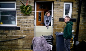 Mytholmroyd residents look out over the flood defences as soldiers arrive to help shore up flood barriers as Storm Dennis begins to make landfall