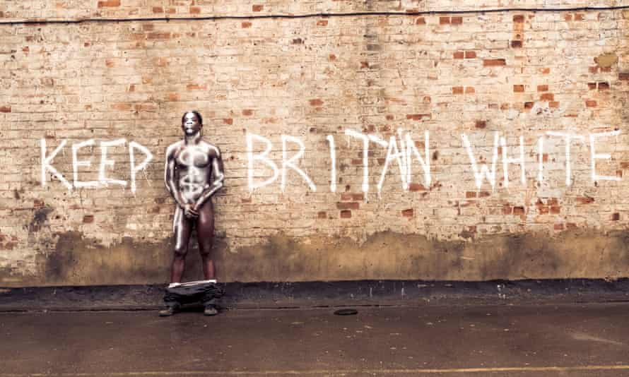 Young naked black male holding his crotch against a wall spray painted along with the words 'keep Britain white'