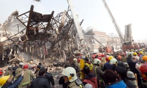 Rescuers and onlookers surround the collapsed tower.