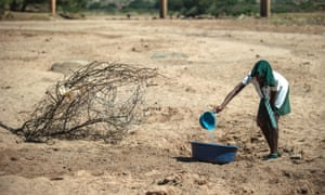 A shool girl tries to collect water from a dry puddle in Nongoma, north west of Durban, that has been badly affected by the recent drought.