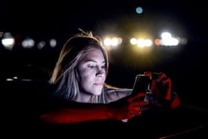 A resident uses her mobile phone at the Distribuidor Altamira, the main exit on the Francisco Fajardo highway, where she can get a signal