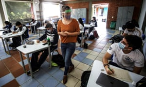 Students attend classes wearing face masks after classes resumed in Cali, Colombia on September 28, 2020, amid the coronavirus pandemic.