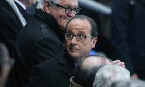 Hollande is escorted out of the stadium by his security team.