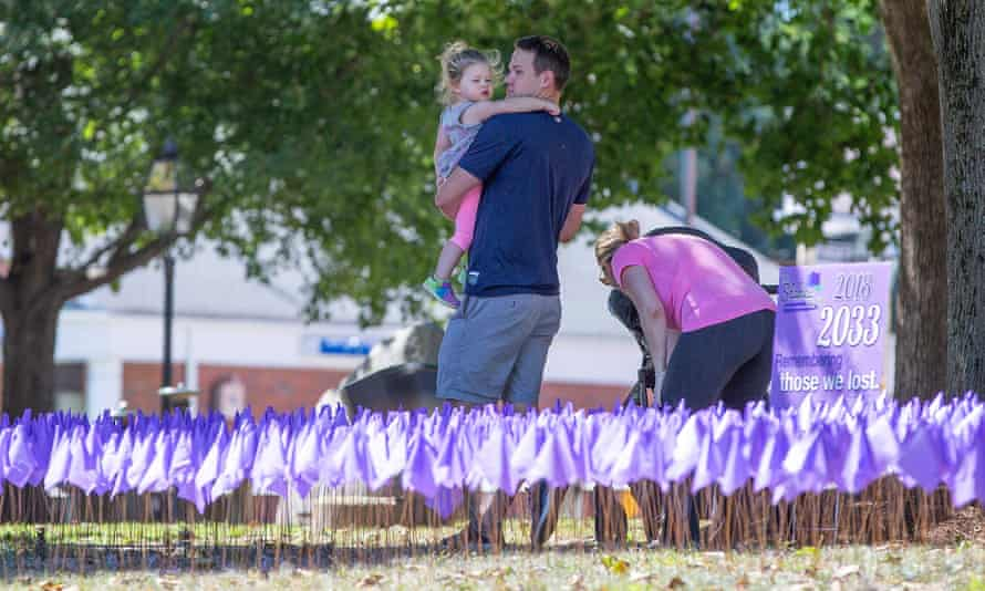 People walk through a patch of purple flags representing the 7893 opioid-related deaths in Massachusetts from 2015 to 2018.