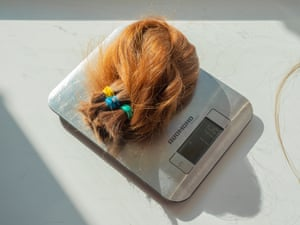 Alina's hair being weighed on a scale after being cut off