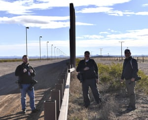 Photographers Jim Watson, Yuri Cortez and Guillermo Arias at metal fence between the US and Mexico in Puerto Palomas