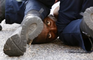 A man protesting the shooting of Alton Sterling is detained by law enforcement officers near the headquarters of the Baton Rouge police department