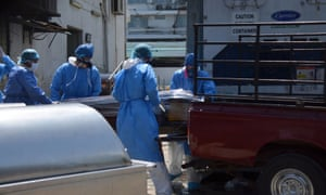 Health workers wearing protective gear load a coffin onto the back of a pick-up truck outside of Teodoro Maldonado Carbo Hospital amid the spread of the coronavirus disease (COVID-19), in Guayaquil, Ecuador April 3, 2020.