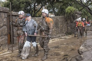 Members of the Heavy Water Search and Rescue team help evacuate a resident along Montecito Creek
