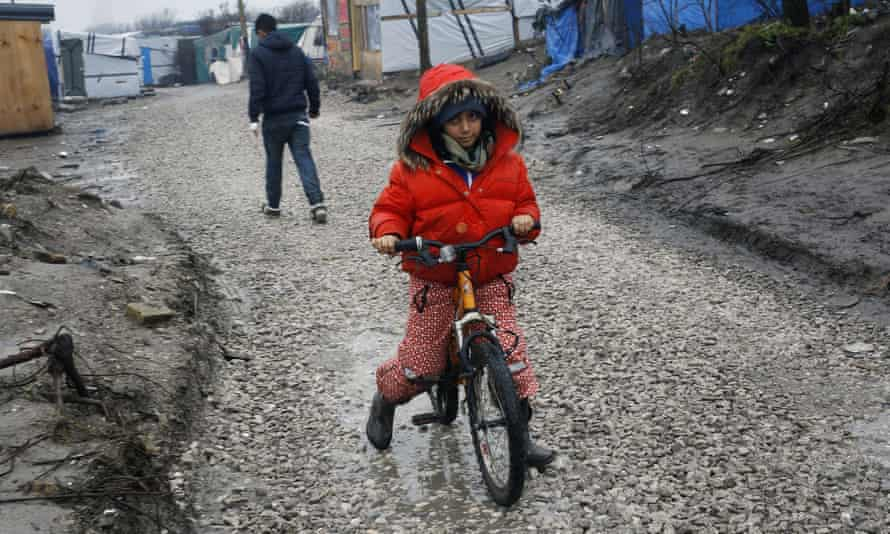 A child rides a bicycle at refugee camp outside Calais