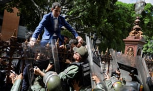 Juan Guaidó attempting to climb over a fence into the assembly's grounds but was repelled by members of Maduro's Bolivarian National Guard.
