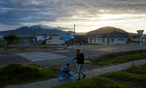 A woman pushes a child on a tricycle in the centre of Yuzhno-Kurilsk, the main settlement on the island of Kunashiri