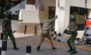 A man covers himself as a riot police officer beats him with a baton during the demonstration against the Independent Electoral and Boundaries Commission.