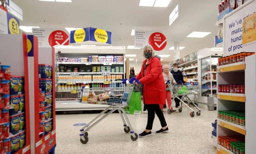 A woman wearing a face mask pushes a shopping trolley at a Tesco supermarket