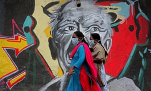 Women walk past a mural painting along a roadside in Bangalore, India, 9 January 2021.