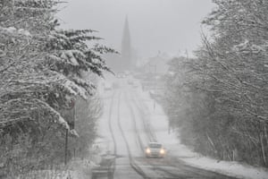 A car on the B718 during a heavy snow shower in Harthill, Scotland