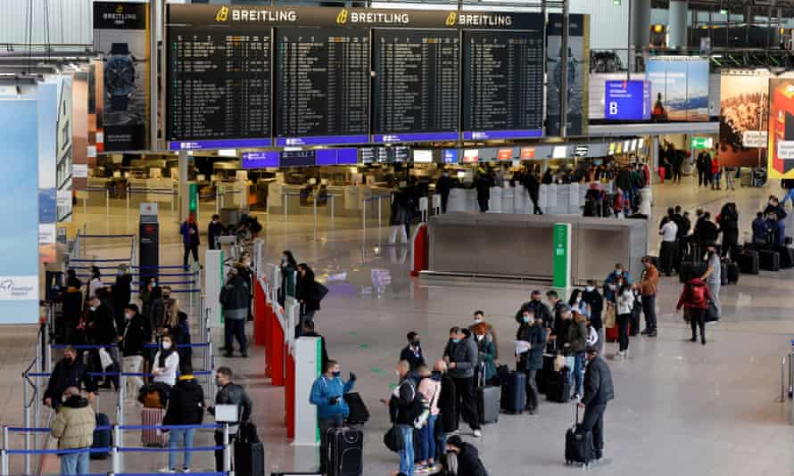 People queue to check in for their flights at Frankfurt airport.