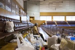 An evacuee rests in a gymnasium in Kurashiki, Okayama