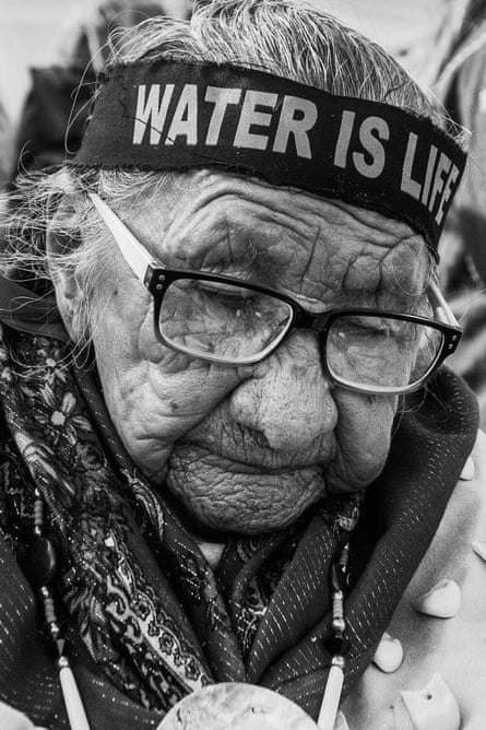 An elder in peaceful prayer and protest, bearing the message of Mni Woc'oni: Water is life.