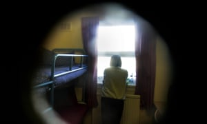 female prisoner seen through the door of her cell