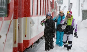 Skiers with skis on shoulders by the train on railway station platform on a snowy day at Switzerland