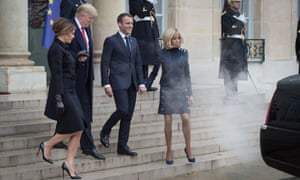 A car exhaust billows in front of the Trumps and Macrons.