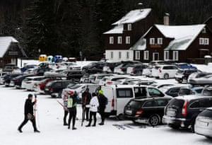 People prepare their skis at a car park in Modrava.