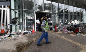 Police officers stand guard as cleaners clear remaining items around the Legislative Council Building after protesters stormed the building in Hong Kong