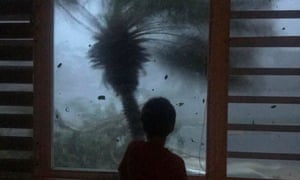A boy watches the strong winds and rain from Hurricane Maria in September 2017.