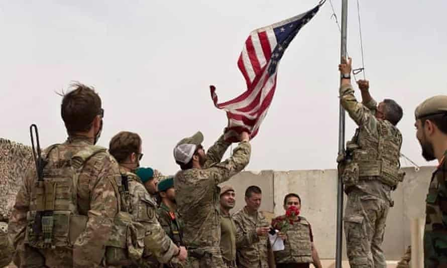 A US flag is lowered as American and Afghan soldiers attend a handover ceremony in Helmand on 2 May 2021.
