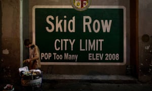 A homeless man takes food from a rubbish bin in Los Angeles' Skid Row area