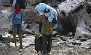 Balaroa residents carry belongings salvaged from their collapsed homes