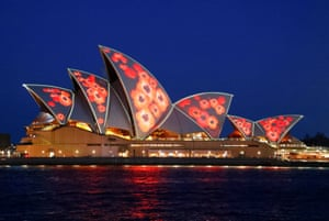 Red poppies are projected onto the sails of the Sydney Opera House