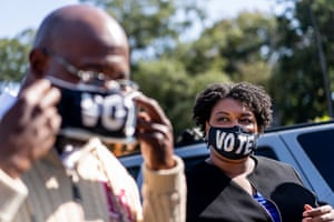 Democratic US Senate candidate Raphael Warnock and Stacey Abrams speak to voters at the Coan recreation center in Atlanta, Georgia, on election day.