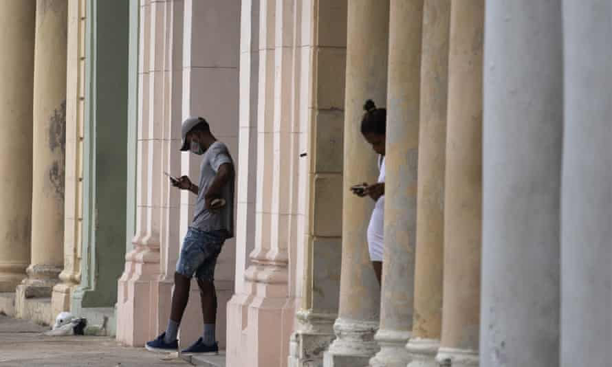 Cubans use their cell phones near to where a pre-paid public wifi connection was working near the Malecon seawall in Havana, earlier this month.