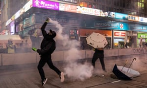 A Hong Kong protester throws a tear gas canister on October 27, 2019